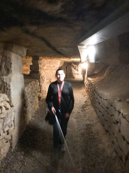 The image shows a dark-haired woman walking in a well-lit tunnel using a white cane.