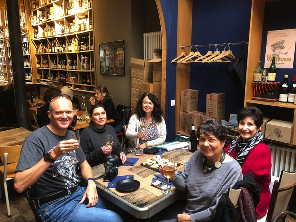 4 people sitting at a table in a wine shop