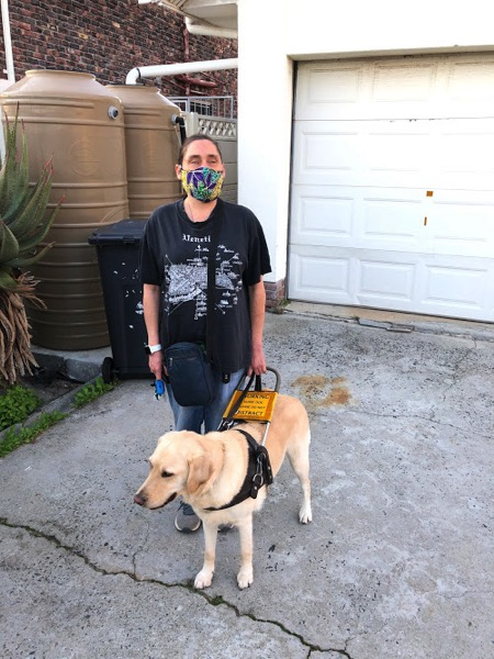 the image shows Lois wearing a brightly coloured mask, standing outside with her guide dog, Fiji.
