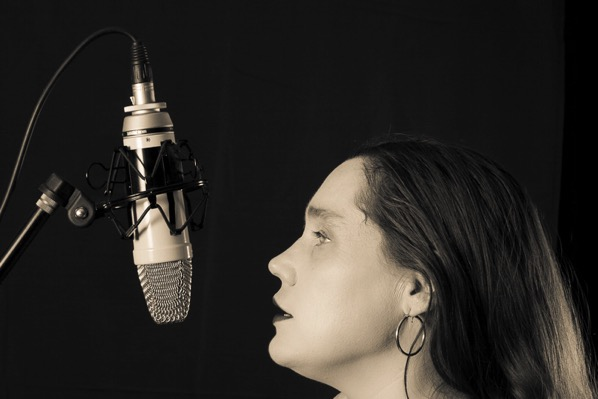 The images shows Lois singing into a microphone