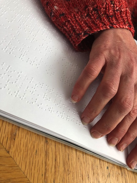 the images show hands tracing across a braille book