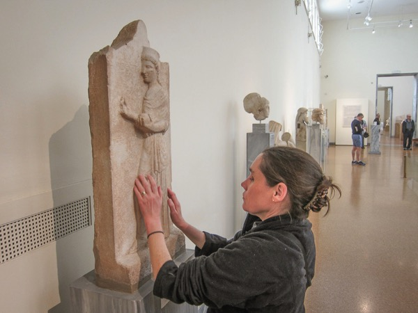 The image shows Lois using her sense of touch to explore the Athens Museum