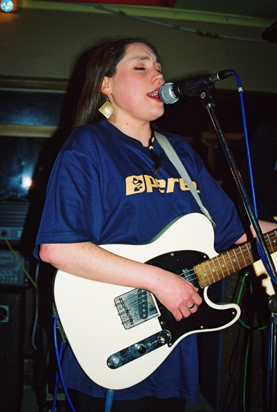the image shows Lois playing guitar and singing into a microphone