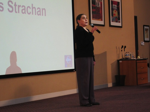 Alt text: the image shows Lois speaking in front of an audience