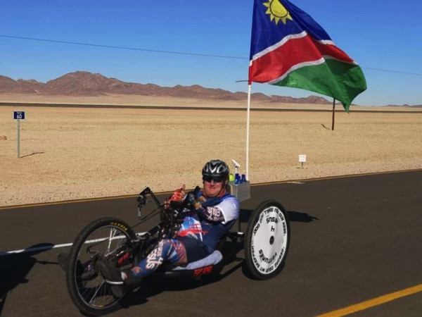 Normie Eckard on his handcycle on a road with a Namibian flag